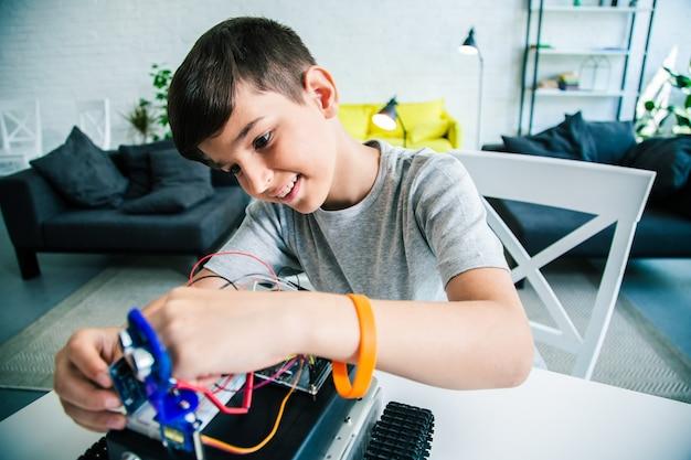 Écolier intelligent positif expérimentant avec son appareil robotique tout en travaillant sur son projet d'ingénierie