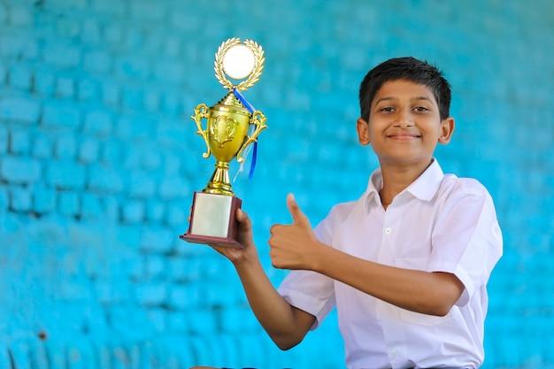 Écolier intelligent soulevant son trophée en tant que vainqueur du concours scolaire.