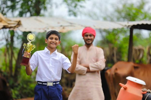 Écolier intelligent tenant le trophée gagnant et debout avec son père