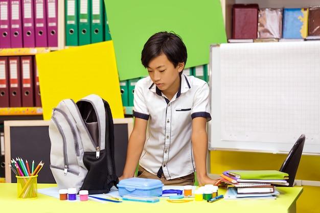 Écolier jeune garçon asiatique portant sac à dos et debout dans la bibliothèque à l'école.