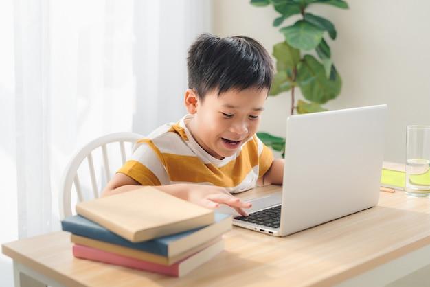 Écolier jouant à un jeu en ligne sur un ordinateur portable à la maison, table assise, temps libre avant l'adolescence