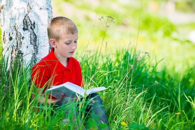 Écolier lisant le livre dans la nature