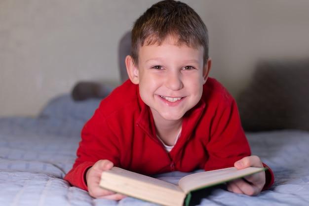 L'écolier lit le livre à la maison, l'apprentissage à distance