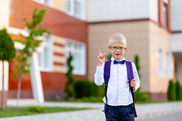 Un écolier avec des lunettes blondes et un sac à dos se tient à l'école et montre un coup de pouce