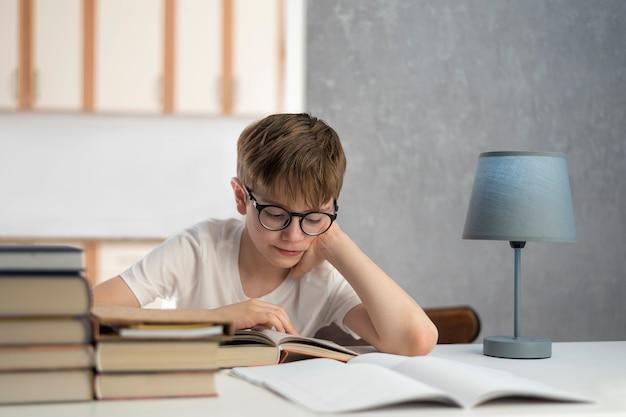 L'écolier à lunettes fait ses devoirs. apprentissage à distance. le garçon lit le manuel. enseignement à domicile
