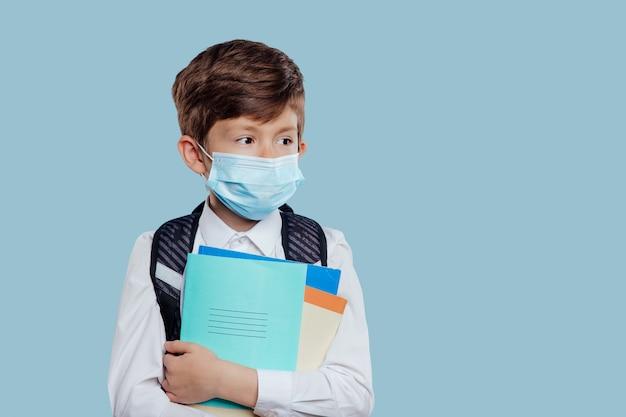 L'écolier avec masque médical et sac à dos a des cahiers et des livres à la main isolés sur fond bleu