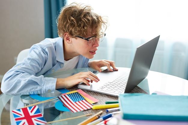 Écolier mignon dit bonjour à la caméra tout en ayant une leçon en ligne à la maison