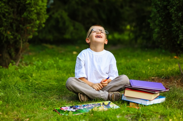 Écolier mignon étudie à l'extérieur sur une belle journée d'automne.