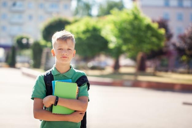 Écolier mignon à l'extérieur par journée ensoleillée. adolescent avec son sac à dos et tenant des livres