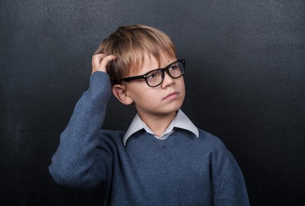 Écolier mignon garçon européen se tient pensivement au tableau noir et se gratte la tête
