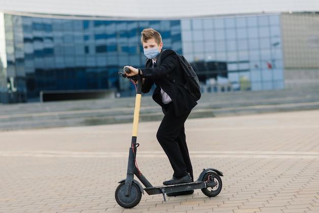 Écolier mignon avec masque de protection conduisant un scooter dans une ville.