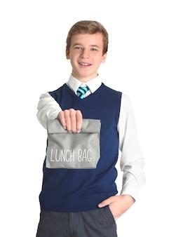 Écolier mignon avec sac à lunch sur l'espace blanc