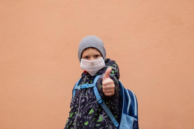 L'écolier montre la classe en masque de protection