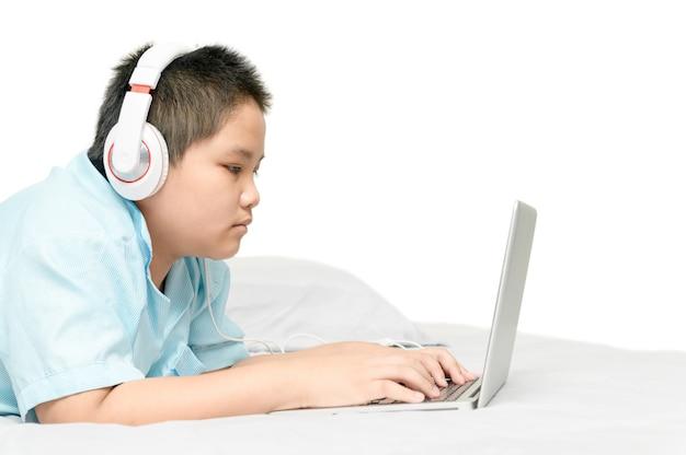 Écolier obèse couché et portant des écouteurs pour apprendre en ligne à partir d'un ordinateur portable sur son lit