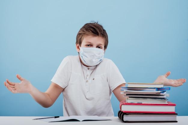 Écolier perplexe avec un masque médical sur le visage tenant des cahiers et des livres à la main en regardant...