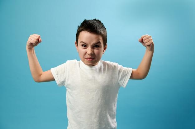 Écolier de pompage des biceps et à la colère à l'avant sur une surface bleue avec copie espace