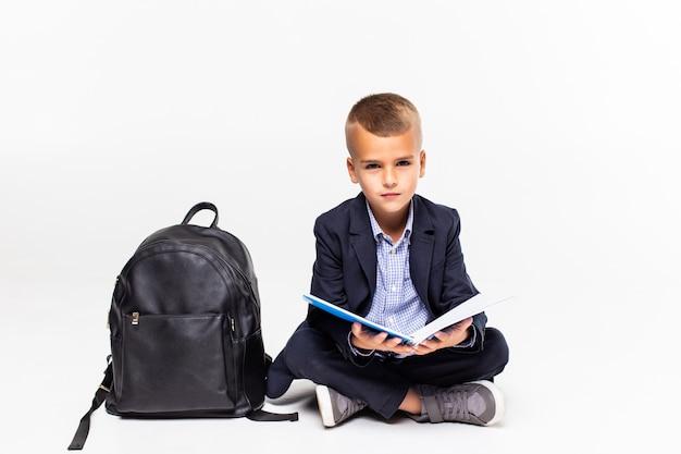 Écolier primaire assis sur le sol et la lecture isolé sur mur blanc