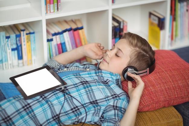 Écolier se détendre sur le canapé tout en écoutant de la musique sur une tablette numérique dans la bibliothèque