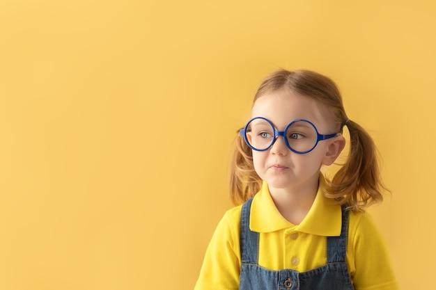 Écolier sérieux dans des verres fond jaune isolé regardant l'espace de copie retour à l'école