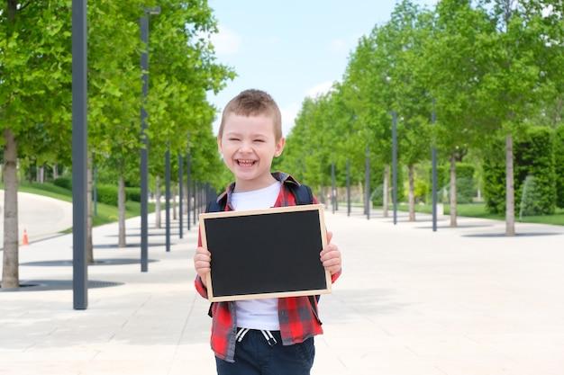 Écolier avec un signe dans ses mains dans la rue sur le chemin de l'école. retour à l'école
