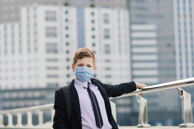 Un écolier sort de l'école avec un masque de protection dans la ville