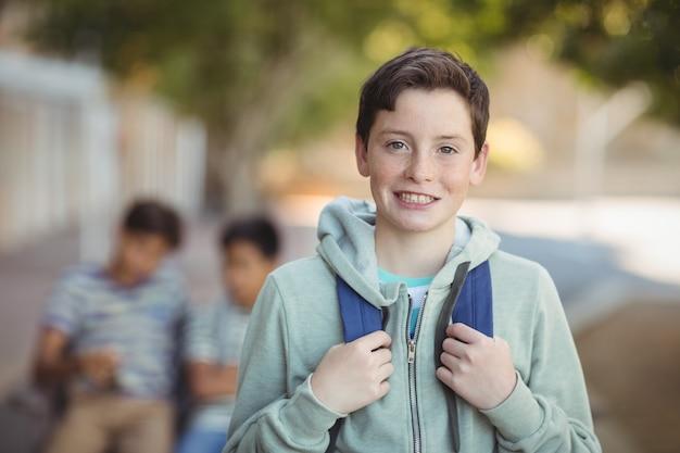 Écolier souriant debout avec cartable sur le campus