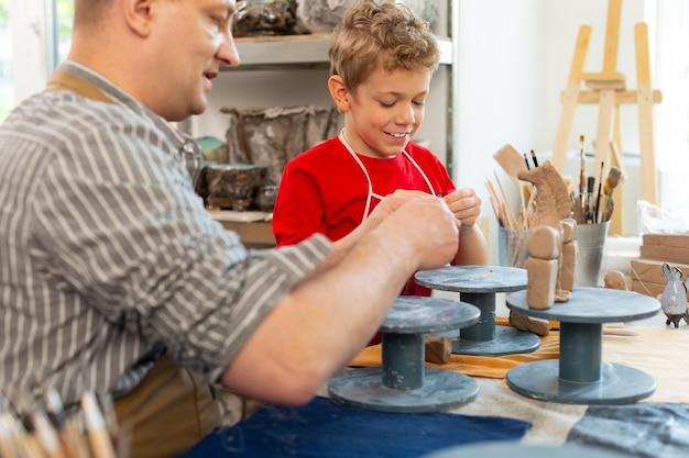 Écolier souriant tout en sculptant des figures d'argile avec enseignant