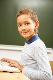 Écolier en tapant sur le clavier d'ordinateur