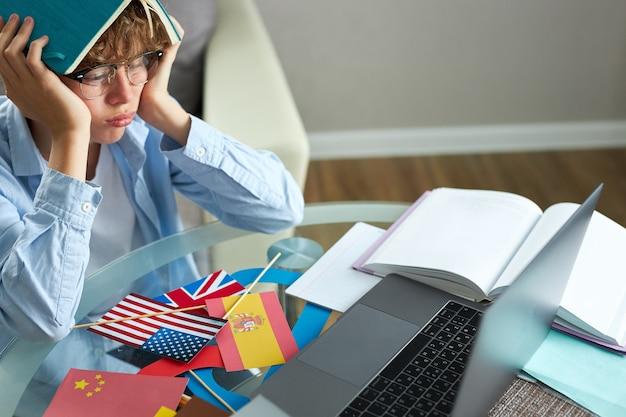 L'écolier tape le rapport sur un ordinateur portable, fait ses devoirs