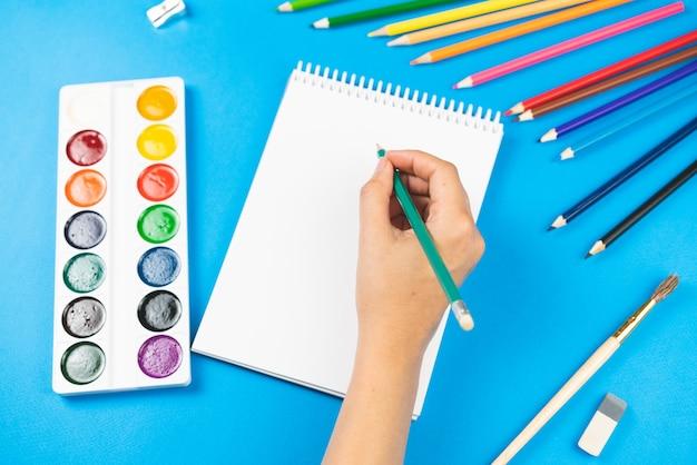 Un écolier tient un crayon sur un bloc-notes sur un espace bleu et des fournitures.