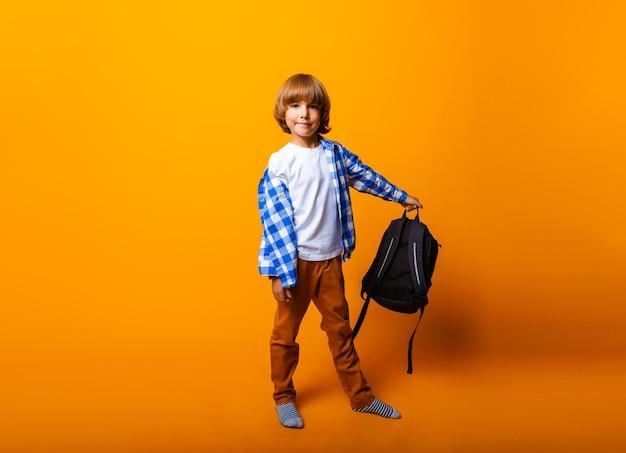 L'écolier tient un sac à dos isolé sur fond jaune.