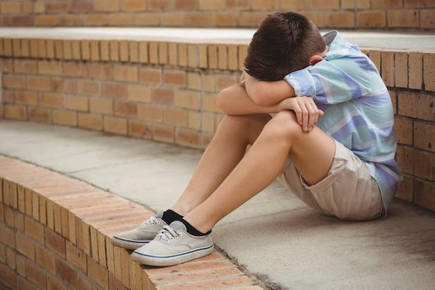 Écolier triste assis seul sur les marches du campus