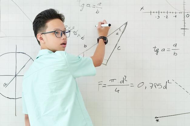 Écolier vietnamien à l'écoute des conseils d'un camarade de classe lors de la résolution d'une tâche de géométrie et d'écriture sur un tableau blanc