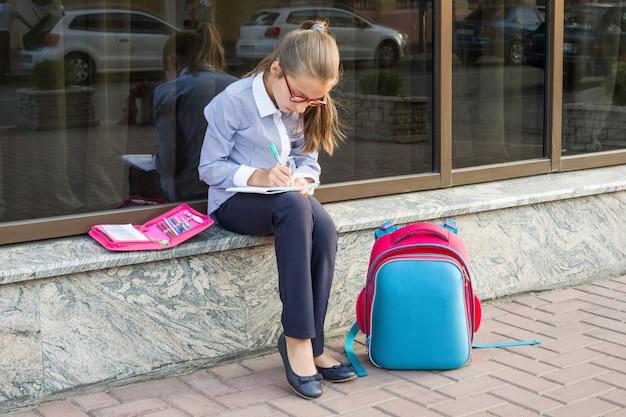 Écolière 10 ans dans des lunettes avec un sac à dos
