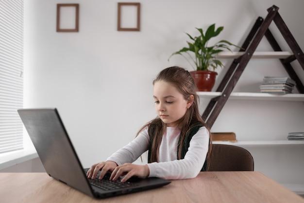 Une écolière accro à internet s'assoit rapidement devant un ordinateur portable