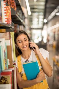 Écolière adolescent avec livre parlant par smartphone