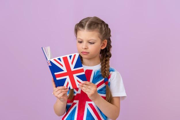 Une écolière apprend l'anglais en lisant un manuel.