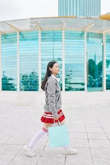Écolière asiatique souriante marchant à l'extérieur avec des sacs à provisions