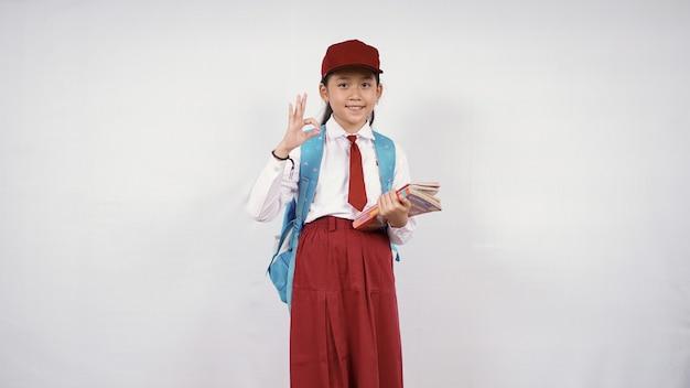 Une écolière asiatique va partir avec des livres et d'accord isolée sur fond blanc