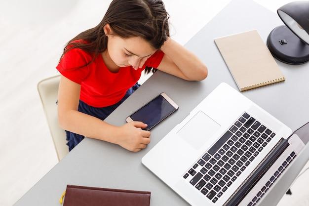 Écolière assez élégante étudiant les devoirs en maths pendant sa leçon en ligne à la maison, distance sociale pendant la quarantaine, auto-isolement, concept d'éducation en ligne, élève à domicile