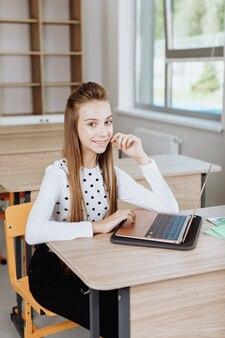 Écolière assise au bureau avec ordinateur