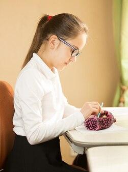 Écolière assise derrière la table et prenant un crayon dans une trousse