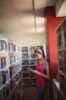 Écolière attentive à l'aide de tablette numérique dans la bibliothèque