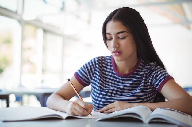 Écolière attentive à faire ses devoirs en classe