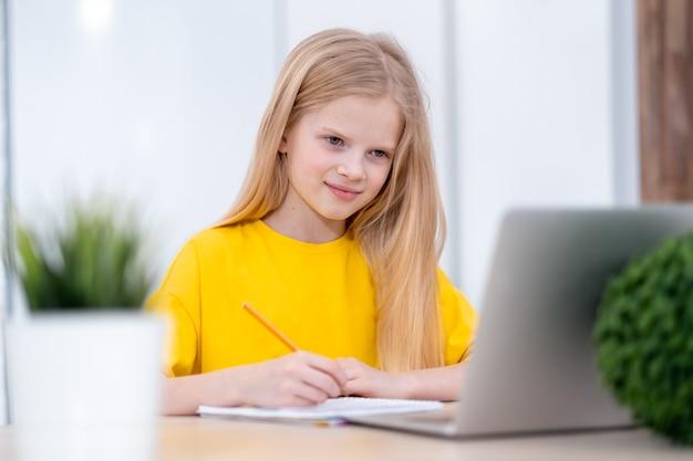 Écolière blonde étudie à la maison à faire ses devoirs avec un ordinateur portable apprentissage à distance en ligne