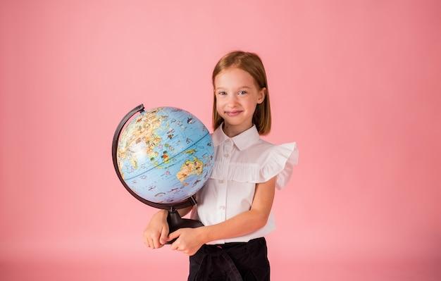 Une écolière blonde en uniforme scolaire tient un globe sur fond rose