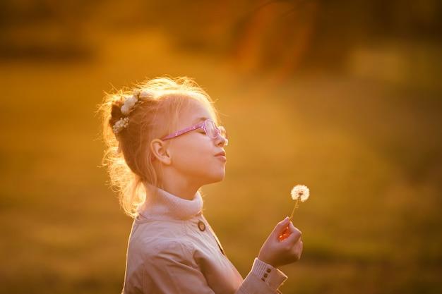 Écolière bouclé dans les lunettes et manteau léger, jouer avec pissenlit dans le parc en automne sur le coucher du soleil