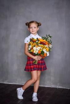 Écolière avec bouquet de fleurs. concept d'école