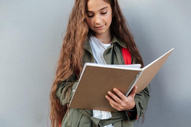 Écolière brune souriante aux cheveux longs vêtue de vêtements chauds