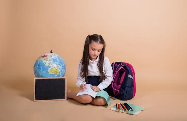 Une écolière brune en uniforme est assise avec des fournitures scolaires et écrit dans un cahier sur fond beige avec une place pour le texte